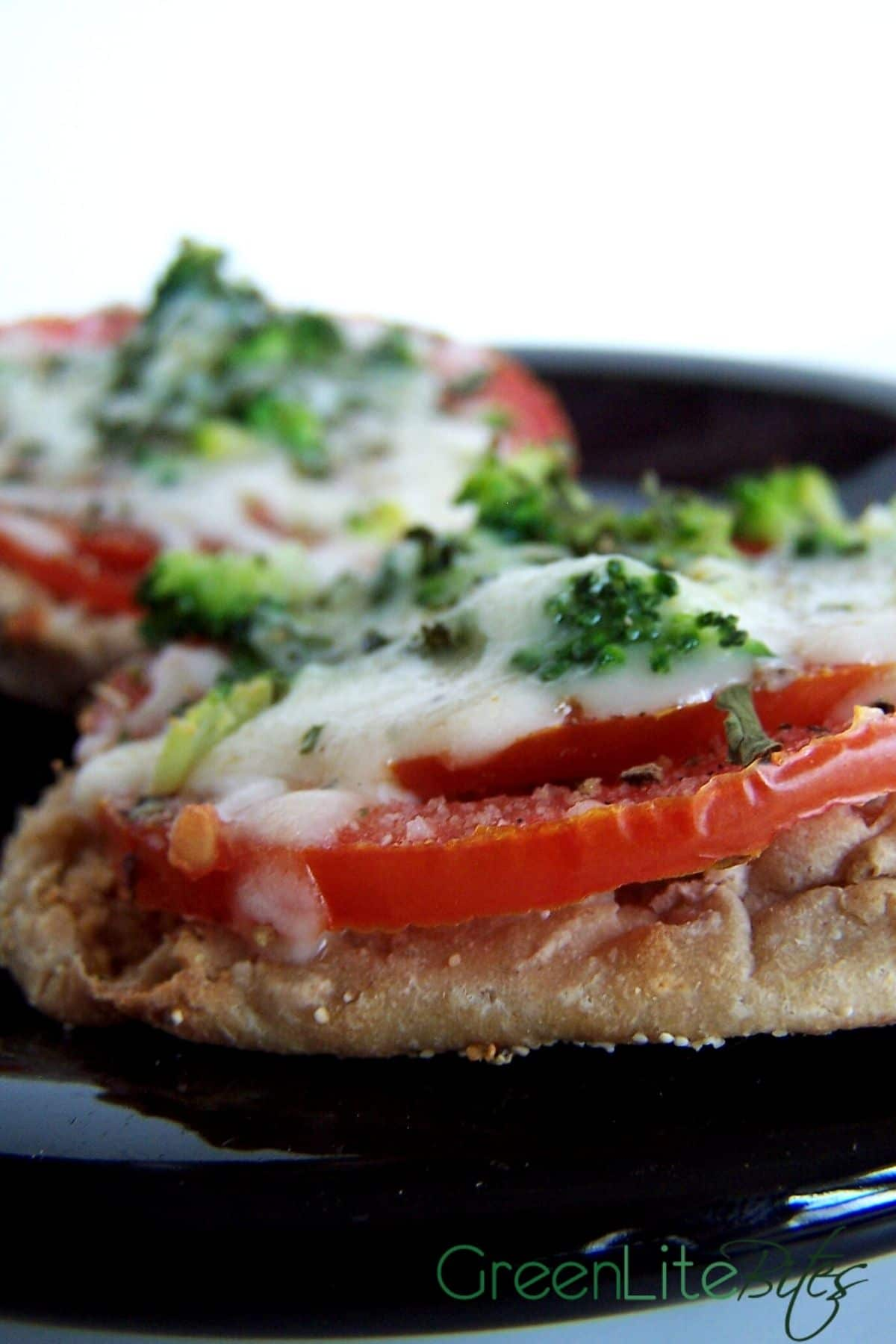 English muffin pizza on black plate