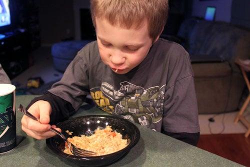 Kids eating chicken oat stew.
