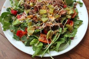 A Sriracha Dressed Bacon Cheeseburger Salad on Plate