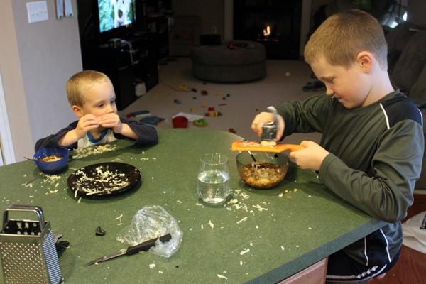 Kids eating soup and grated cheese.