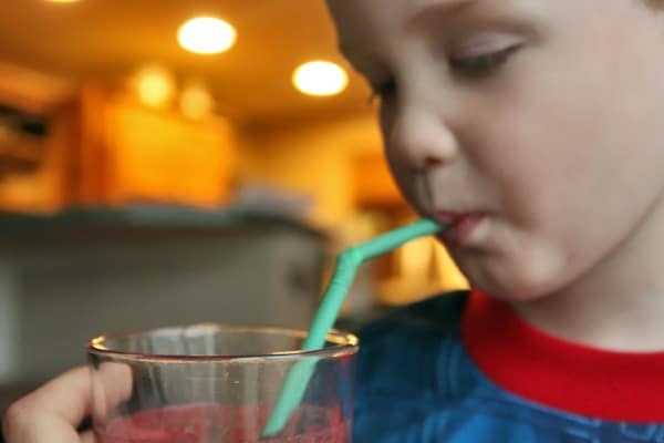 toddler drinking Beet Smoothie with Blueberries and Pineapple