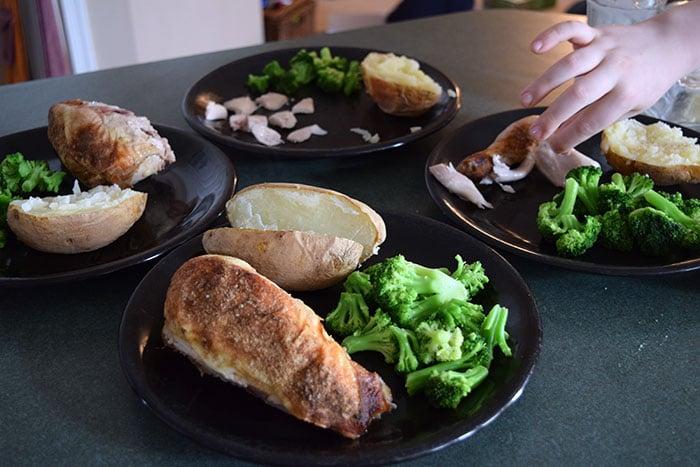 Kids stealing chicken off plate