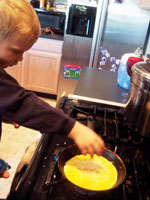 The toddler adding cheese to the omelet